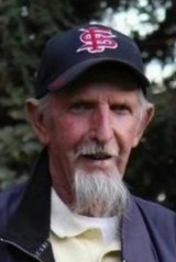 Photo of Chet Scharnick, an older man wearing a Cardinals baseball cap, sporting a wispy white goatee and mustache.