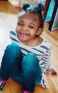Photo of Zha-Nae Wilkerson, a small African-American girl sitting on the floor, knees pulled up to her chest, smiling for the camera.
