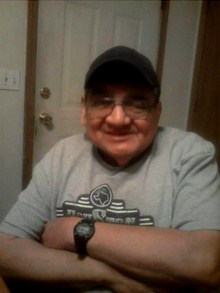 Photo of Elvis Dry, an older man with fair skin and a large nose, grinning at the camera with his arms folded. He is wearing glasses, a baseball cap, a sweater, and a wristwatch.