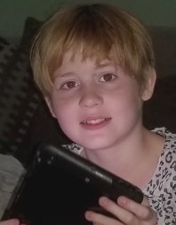 Photo of Chloe Hobbs, a girl with fair skin and strawberry-blonde hair in a boy cut. She is holding a tablet PC and gazing at the camera withe a slight smile on her face.