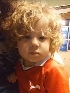 Photo of Dante Mullinix, a small boy with a mop of curly blond hair, wearing an orange polo shirt and looking at the camera.