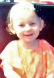 Photo of Kendall Chick, a toddler girl wearing an orange dress. Her pale skin is washed out by sunlight, and she is wearing a hair ribbon with a black flower in her wispy blonde hair. She is smiling.