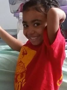 Photo of a young African-American girl wearing an oversized red T-shirt. Her hair is done in braids; she has an arm behind her head, and she is smiling.