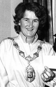 Black and white photo of Janette Dunbavand as a younger woman. She has short curly dark hair and pale skin; she is wearing a white robe and a mayor's chain of office.