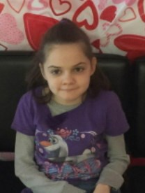 Photo of Ashlyn Ellis, a young girl with long brown hair, looking at the camera, biting her lower lip. She is wearing a purple sweater.
