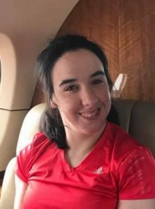 Photo of Rebecca Fogel, a young woman sitting in an airplane seat, wearing a red T-shirt and smiling for the camera. Her messy dark-brown hair is drawn back in a half-ponytail.