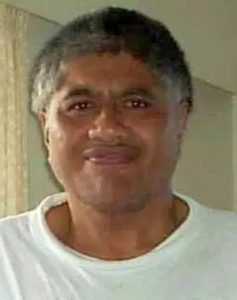 Photo of Bruce Rangitutia, a middle-aged man smiling awkwardly at the camera. He is wearing a white T-shirt; his skin is tan, and his hair is salt-and-pepper, cut short.