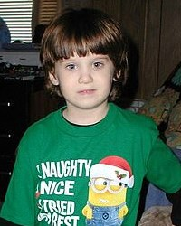 Photo of a small boy with dark hair and pale skin, wearing a green Minions T-shirt