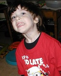 Photo of a boy with dark brown hair and pale skin, wearing a red Minions T-shirt and smiling awkwardly for the camera