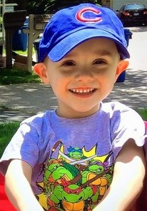 Photo of a small boy in a big blue baseball cap and Teenage Mutant Ninja Turtles T-shirt. He has pale skin and his ears stick out, and he is smiling, showing he still has all his baby teeth.