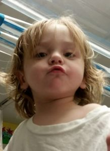 Photo of a toddler boy with a halo of blond hair, pursing his lips at the camera.