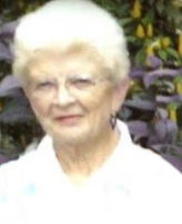 Photo of a white-haired old woman wearing glasses and a white blouse.