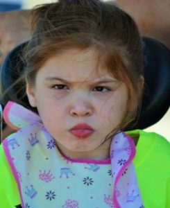 Photo of a young girl sitting in a wheelchair, her hair messy, lips pursed, looking annoyed.