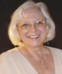 Photo of an older woman with white hair and pale skin, in a formal blouse and silver necklace.