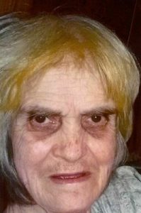 Photo of an older woman with straight white hair dyed partly blonde and dark circles under her eyes.