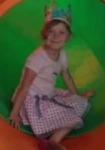 Photo of a girl in a polka-dot skirt, sitting in a play tunnel.