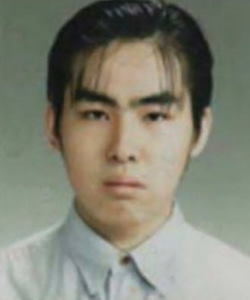 Formal photo of a young, unsmiling Japanese man.