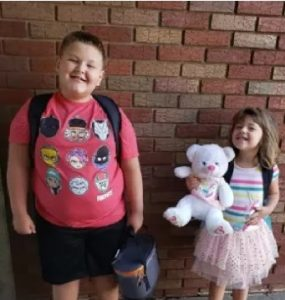 Photo of Conner and Brinley Snyder. He is a heavyset boy wearing a T-shirt, shorts, and backpack; she is a girl wearing a frilly pink skirt and holding a white teddy bear.