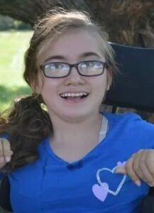 Photo of a teenage girl with a dark-blonde ponytail and glasses, sitting in a wheelchair.