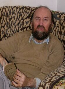 Photo of a middle-aged man in a cardigan, sitting in a living chair and reading a book.