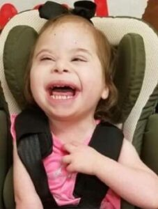 Small girl with Down syndrome in a car seat, grinning at the camera.
