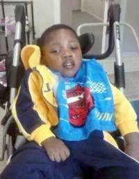 "Photo of a young boy in a wheelchair, wearing a ""Cars"" sweatshirt."