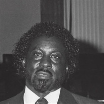 Black and white photo of a dark-skinned man in a suit; his hair is short and curly, and he has a mustache and beard.