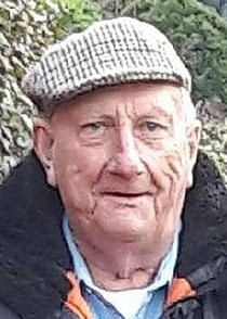 Photo of an elderly man with a tweed cap and wool jacket.