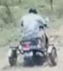 Blurred photo, taken from behind, of a person in a white shirt riding a three-wheeled scooter down a dirt road.