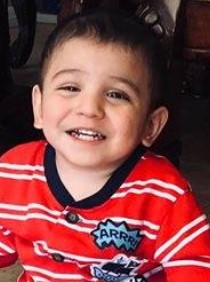 Photo of a small, smiling boy waearing a red striped shirt.