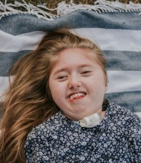 Photo of a girl lying on a striped blanket. Her skin is fair and her long hair is strawberry-blonde. She is smiling broadly and wearing a black-and-white flowered shirt and a trach collar.