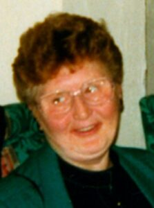 Photo of an older woman with pale skin and red cheeks, her short curly hair colored auburn. she is wearing glasses and smiling for the camera.