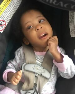 Photo of a toddler girl in a car seat. She is wearing a pink onesie and her hands are balled into fists. Her skin is tan and her eyes are dark brown.