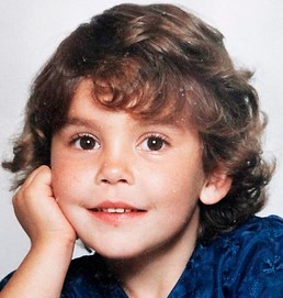 Phot of a small girl with fair skin, brown eyes, and curly brown hair. She is leaning her head against her hand and smiling for the camera.