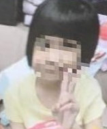 Photo of a toddler girl with dark hair and light skin, face blurred to obscure her identity.