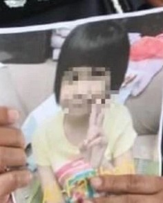 Photo of a toddler girl with straight black hair and pale skin, wearing a yellow T-shirt; her face is blurred to conceal her identity.
