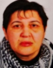 Blurry photo of a middle-aged woman wearing a black-and-white checked scarf. Her hair is tied back.