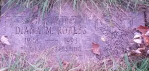 """Photo of an overgrown gravestone. It reads, """"Wife and mother Diana M. Robles. 1948-1993. To life everlasting."""""""