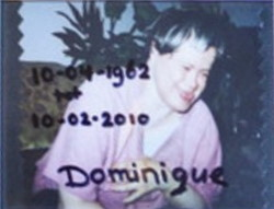 Blurry photo of a woman with Down syndrome. She is wearing a pink shirt, and her eyes are scrunched up in laughter, her tongue poking slightly from her mouth. She has pale skin and short brown hair with blonde streaks.