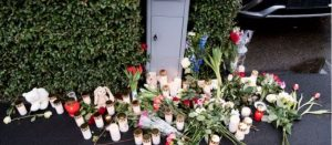 Flowers and candles left by neighbors as a memorial.