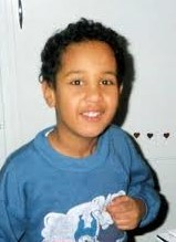 Photo of a young boy with curly black hair and tan skin, wearing a blue shirt. He is smiling for the camera.