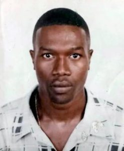 Photo of a black man with short hair, wearing a white button-up shirt.