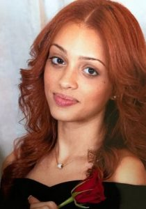 Photo of a woman with red hair, light-brown skin, and light make-up, wearing a black dress and holding a rose.