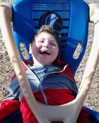 Photo of a smiling boy lying in an adapted swing.