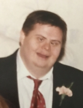 Photo of a heavyset, light-skinned man with Down syndrome. He has dark short hair and is wearing a suit. He is smiling for the camera.