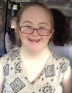 Photo of a young woman with Down syndrome; she has very fair skin and fine blonde hair, and her maroon glasses are slipping down her nose. She is smiling.