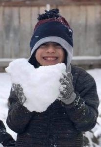 Photo of a smiling boy in a winter hat and coat, holding a chunk of snow in his gloved hands.