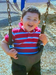 Photo of a small boy sitting in a swing and smiling broadly at the camera.