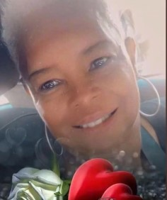 Photo of Callie Branch, a middle-aged woman with brown skin and a pleasant smile; a filter has been applied that adds white roses and a heart.