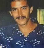 Photo of a man with a mustache, wearing a dark blue shirt.